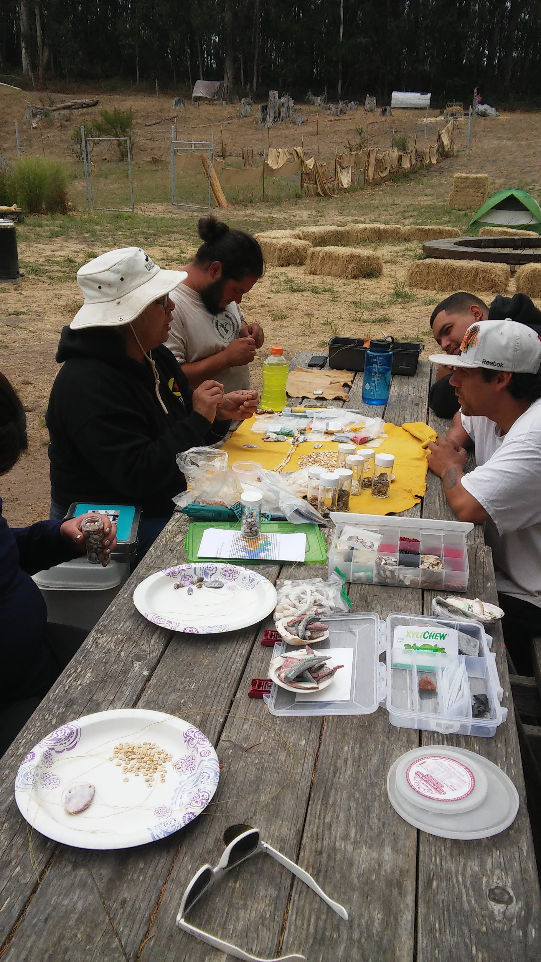 Tribal Elder Eleanor Castro leads a beading workshop with the Native Stewards. During NSC, the stewards participate in daily cultural and educational activities to strengthen a sense of Mutsun identity.