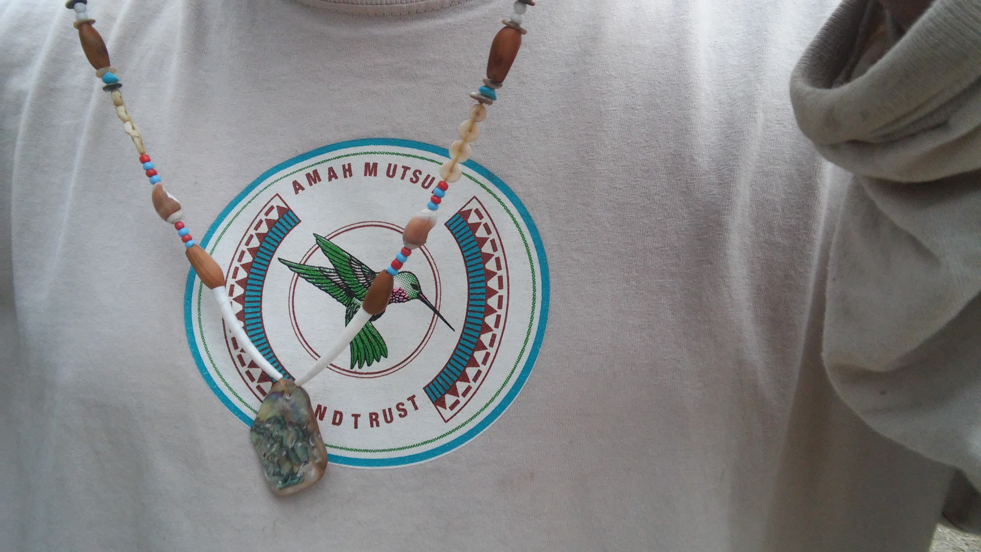 Native Steward Paul Lopez displays an abalone pendant necklace he made from Ender Nora's beading workshop.