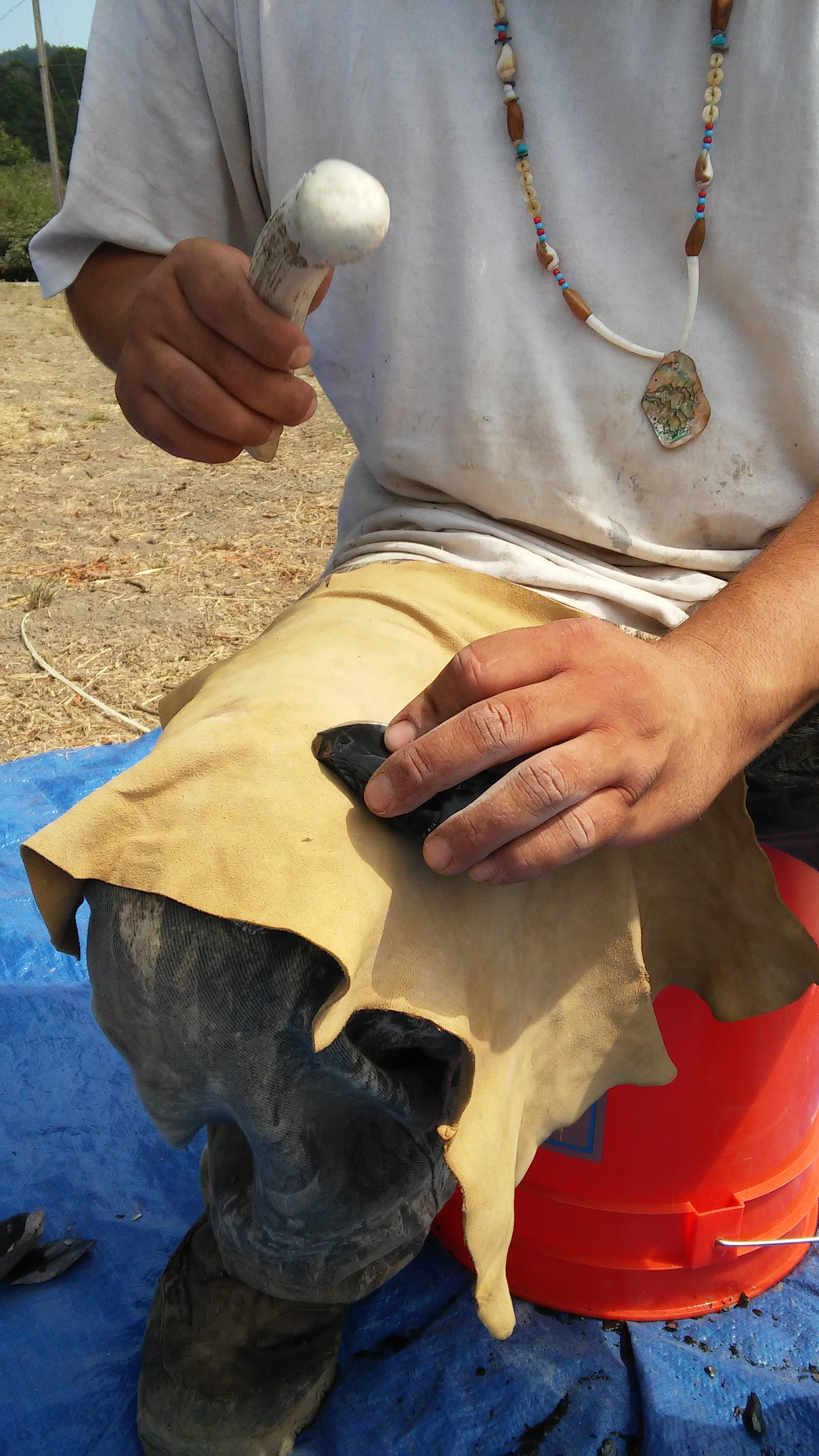 Native Steward Paul Lopez uses an elk antler to flake an obsidian core in an arrowhead-making demonstration. Native Stewards learn and practice traditional crafts and skills at Stewardship Corps, keeping skills like flintknapping alive within the Amah Mutsun Tribal Band.