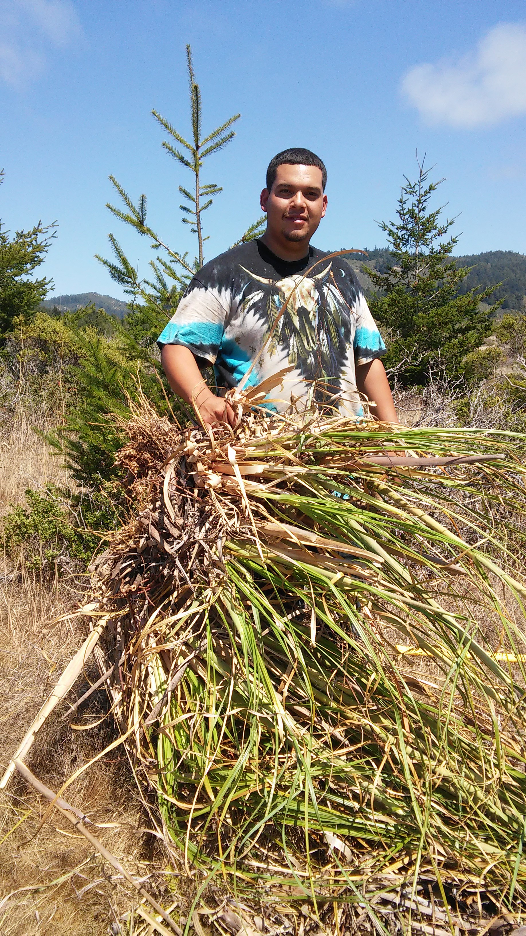 Native Steward Nathan Vasquez with the root ball of a clump of Pampas grass, recently removed from the Costanoa Easement.