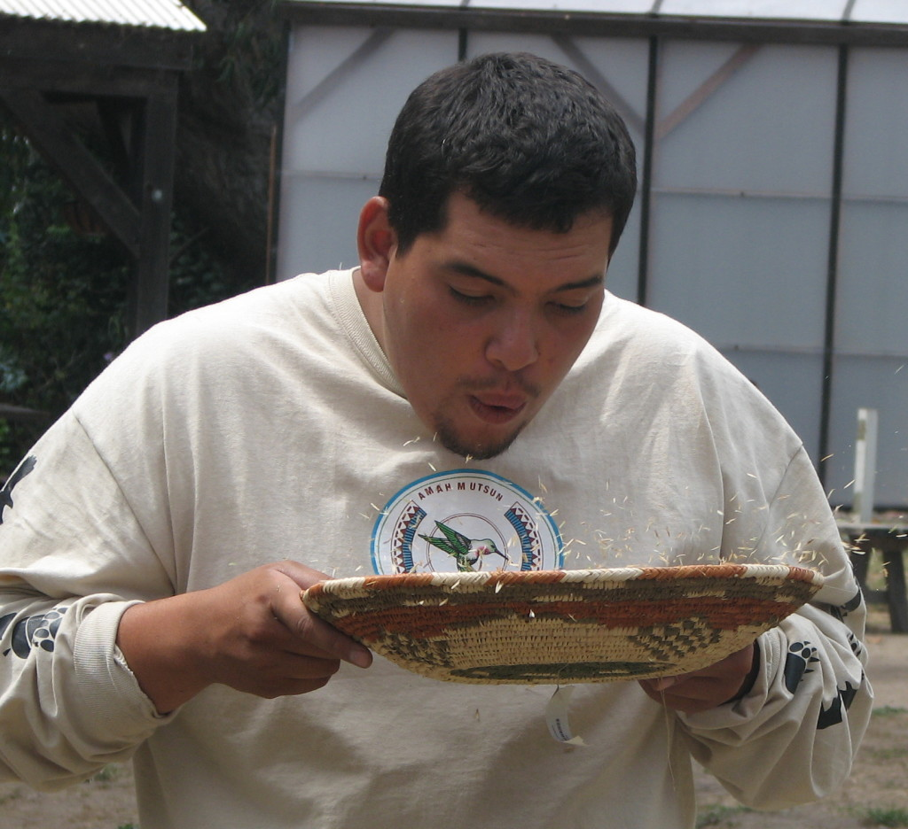 Native Steward Nathan Vasquez blows chaff off of California Brome seeds during a pinole-making demonstration. Photo courtesy Rick Flores.