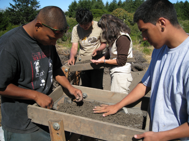 Amah Mutsun Tribal Band members Ernie and Angelo Pineida (foreground) and UC Berkeley students (background) screen deposits from an archaeological site in Quiroste Valley, 2008. Photo courtesy Chuck Striplen.