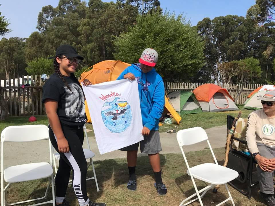 Members of the Wassaka (Condor) group share their team flag. Photo courtesy Abran Lopez.